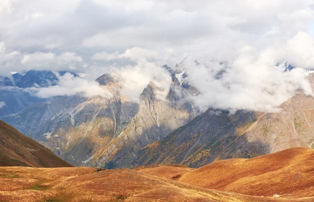 Fantastyczne ośnieżone góry w pięknych chmurach cumulus. główny grzbiet kaukaski. wpisz mount ushba meyer, georgia