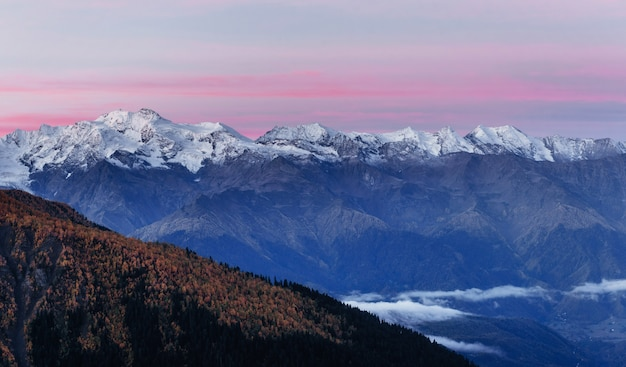 Fantastyczne ośnieżone góry w pięknych chmurach cumulus.