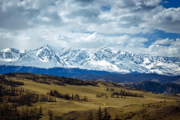 Fantastyczny górski krajobraz. skaliste góry z ośnieżonymi szczytami, wzgórza pokryte trawą w alpejskiej scenie w jasny jesienny dzień z niebieskim niebem i chmurami. widok na step i ośnieżone góry