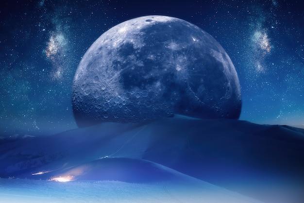 Fantastyczny nocny górski krajobraz z ogromnym księżycem, który spadł z nieba i leży nad górami.