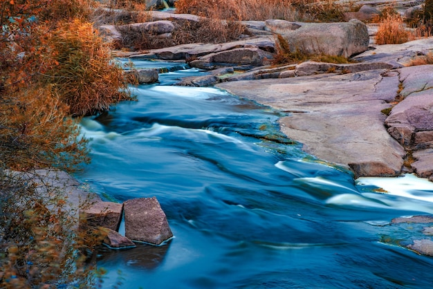 Fantastyczny szybki strumień płynie wśród białych mokrych kamieni pokrytych pożółkłą złotą trawą chłodną jesienią po malowniczej przyrodzie ukrainy