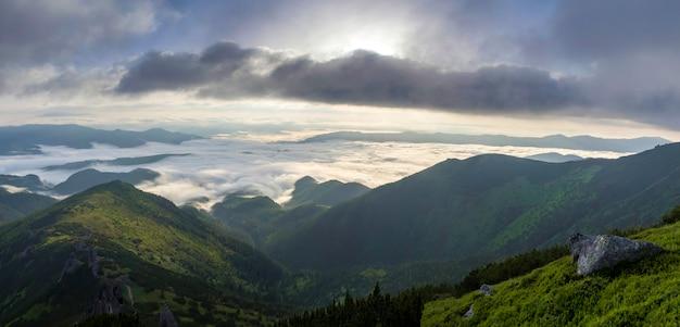 Fantastyczny widok na górską dolinę pokrytą niskimi białymi bufiastymi chmurami jak śnieg rozciągający się do mglistego horyzontu pod jasnym porannym niebem z jasnopomarańczowym blaskiem o wschodzie słońca. pojęcie piękna przyrody.