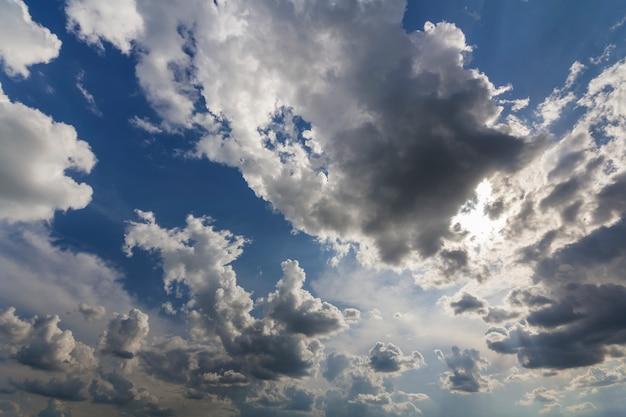 Fantastyczny widok na jasne, białe bufiaste chmury oświetlone słońcem rozpościerającym się na ciemnoniebieskim letnim niebie poruszającym się z wiatrem.