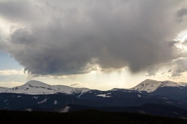 Fantastyczny widok ogromnej białej ciemnej przejmującej burzowej chmury pokrywającej błękitne niebo nisko nad górami hoverla i petros w karpatach z jasnym śniegiem na szczytach. piękno i moc natury.