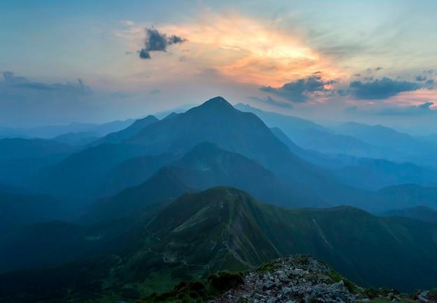 Fantastyczny wschód lub zachód słońca nad zieloną górską granią pokrytą gęstą niebieską mgłą. jasne pomarańczowe słońce wznoszące się w miękkie zachmurzone niebo nad odległym horyzontem. piękno przyrody, turystyki i koncepcji podróży.