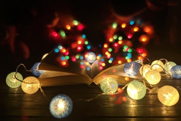 Fantasy czytanie magicznego obrazu otwartej księgi antycznej na drewnianym stole z nakładką z brokatem.