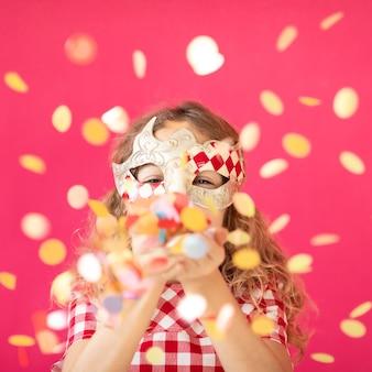 Fantazyjna dziewczyna dmuchająca konfetti na różowy bakground szczęśliwe dziecko bawiące się na karnawale koncepcja wakacji mardi gras