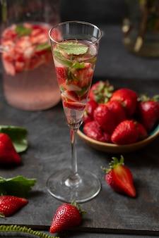 Fantazyjna szklanka pod wysokim kątem z wodą z dodatkiem truskawek