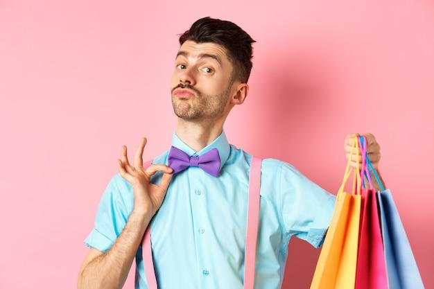 Fantazyjny facet z wąsami poprawiający muszkę i trzymający torby na zakupy, chłopak przynosi paczki z prezentami, stojący nad różem.