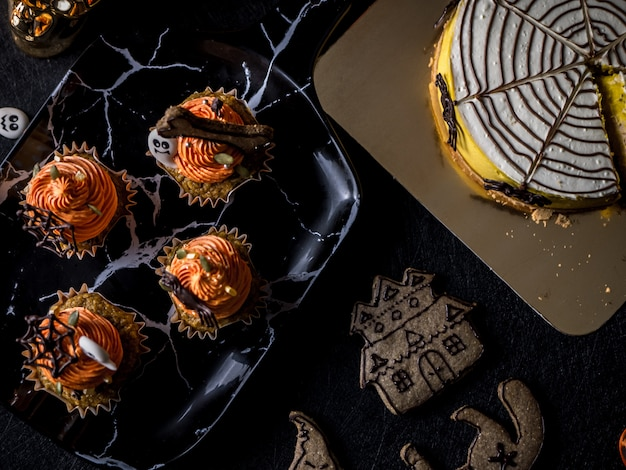 Fantazyjny halloweenowy stół na przyjęcie z dyniową babeczką i ciastkami