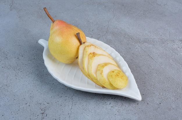 Fantazyjny talerz z gruszką serwowany na marmurowym tle.
