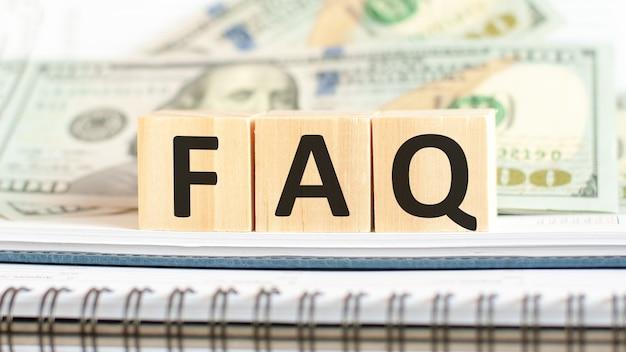 Faq. faq - skrót od często zadawanych pytań. koncepcja biznesowa na drewniane kostki i dolary