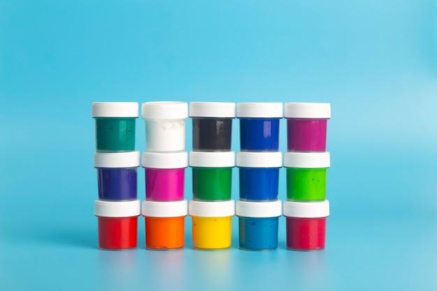 Farba akrylowa w różnych kolorach na niebieskim tle. farba do malowania.