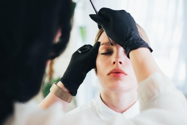 Farbowanie i modelowanie brwi. dziewczyna w salonie piękności.