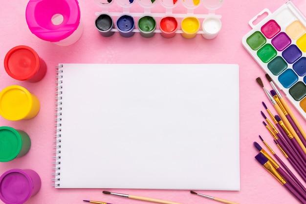 Farby akwarelowe, gwasz, pędzle i paleta do rysowania na różowym tle. skopiuj miejsce.