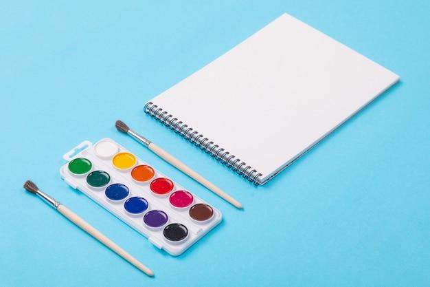 Farby akwarelowe i pędzel z albumu do malowania na białym tle na niebieskim tle