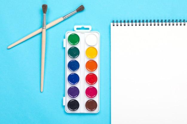 Farby akwarelowe i pędzel z albumu do malowania na białym tle niebieski