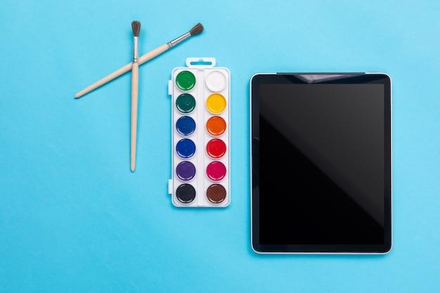 Farby akwarelowe i pędzel z tabletem na niebiesko