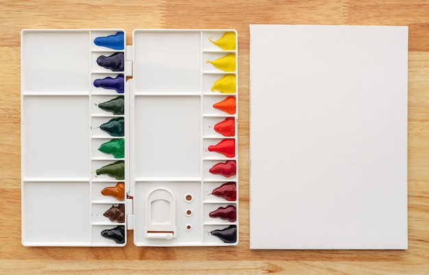 Farby akwarelowe w białej palecie na tle białej księgi. kolorowe wielokolorowe farby akwarelowe w pudełku z farbami.