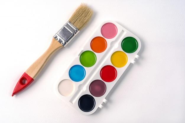 Farby akwarelowe w białym polu i pędzlem, na białym tle