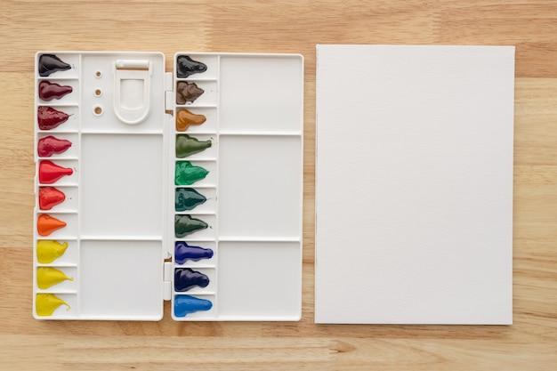 Farby akwarelowe z białym papierem. jasne wielokolorowe farby akwarelowe do tła artystycznego.