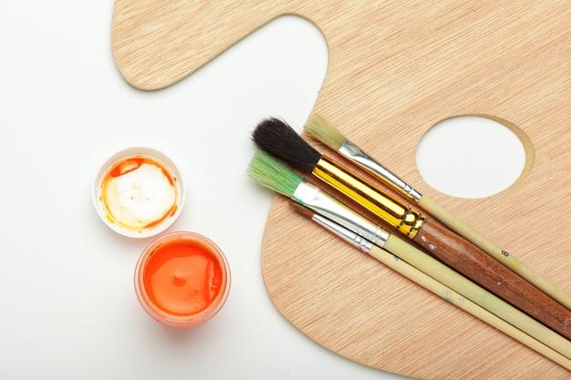 Farby i pędzle, akcesoria artystyczne na białym tle
