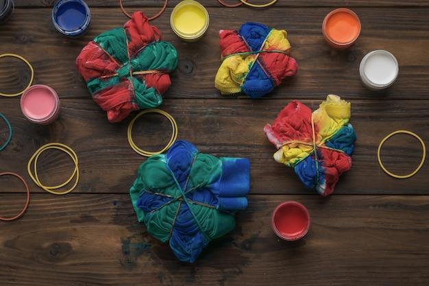 Farby i półfabrykaty do malowania w stylu tie dye na drewnianym tle. tkanina bejcowana w stylu tie dye.