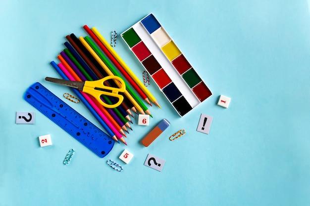 Farby, ołówki, linijka, gumka, cyfry. zestaw akcesoriów szkolnych na niebieskim papierze