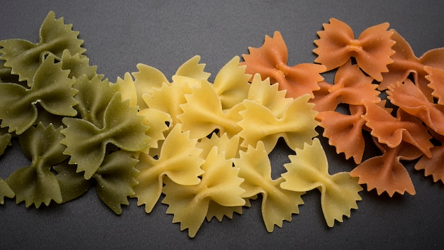 Farfalle świeży makaron w kolorze zielonym; żółte i pomarańczowe kolory nad blatem kuchennym