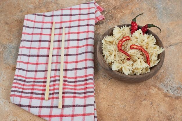 Farfalle z papryczką chili i przyprawami w drewnianej misce. wysokiej jakości ilustracja