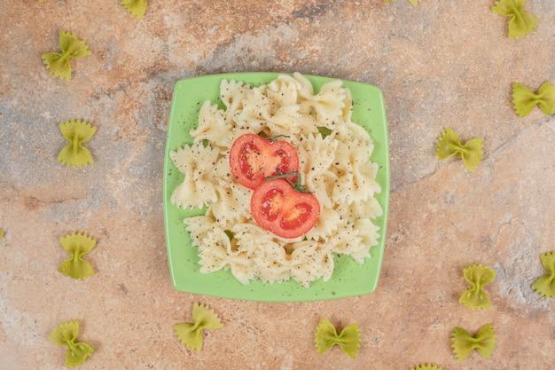 Farfalle z plastrami pomidora na zielonym talerzu.