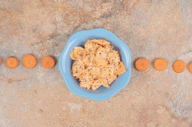 Farfalle z sosem serowym i plastrami marchewki na pomarańczowej przestrzeni.
