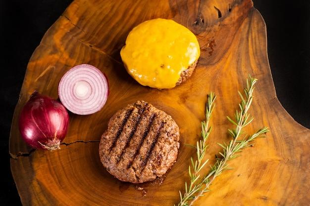 Farm organic gourmet burger, fioletowa cebula i ser do topienia na rustykalnym drewnianym stole. widok z góry