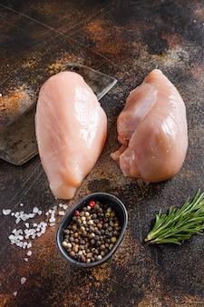 Farm surowa pierś z kurczaka z filetem z rozmarynu i pieprzu, na mięso tasak przyprawy i zioła onold rustykalny metalowy widok z boku.