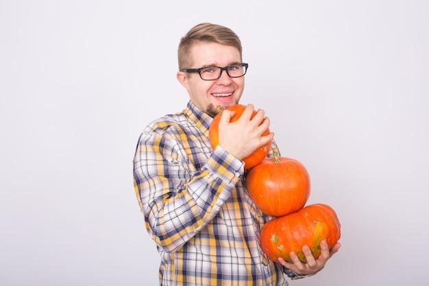Farma jesiennych ludzi koncepcja młody szczęśliwy człowiek rolnik w okularach z dyniami uśmiechający się nad bielą