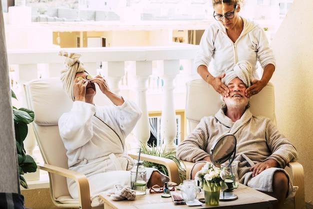Farma piękności na tarasie domu z asystą robienia masaży na twarzy dojrzałego mężczyzny - seniorów razem wypoczywających