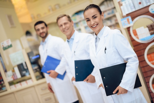 Farmaceuci stoją w aptece i przechowują teczki z papierami