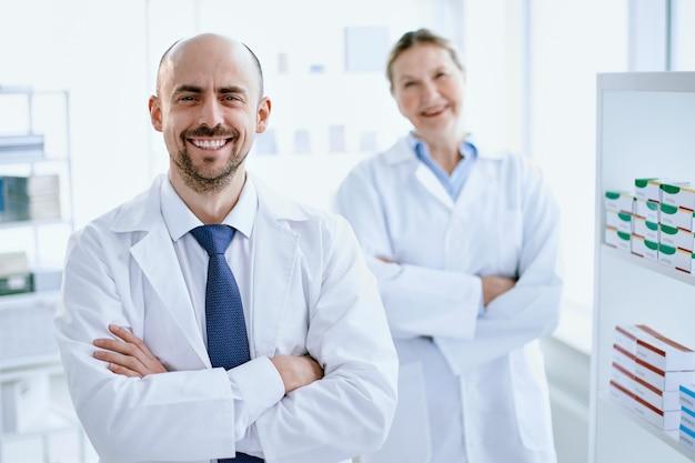 Farmaceuta i jego asystent stojący przy gablocie z lekami