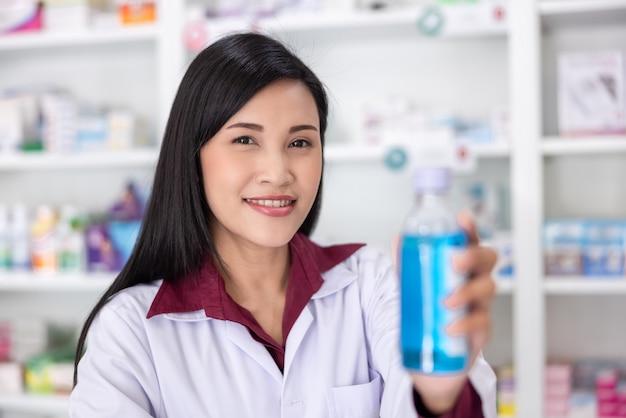 Farmaceuta pokazuje butelkowy żel do rąk w aptece