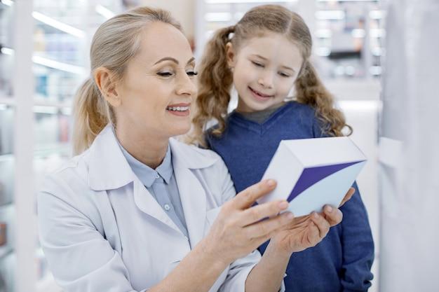 Farmaceuta pomaga małej dziewczynce w aptece