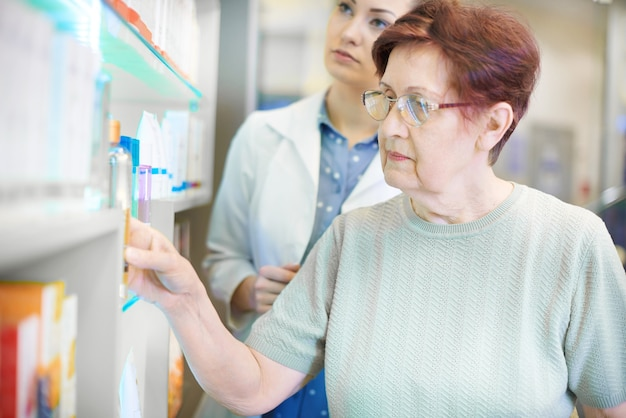 Farmaceuta pomaga starszej kobiecie z receptą