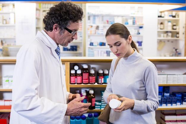 Farmaceuta pomagający klientowi butelkę leku
