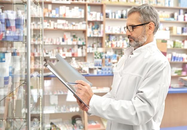 Farmaceuta stojący w aptece z folderu w ręce.