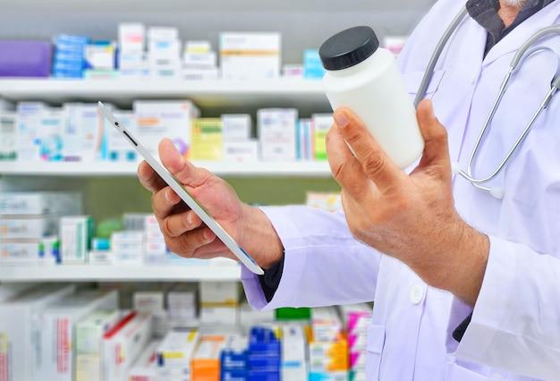 Farmaceuta trzymając butelkę leku i tablet komputerowy do wypełniania recept