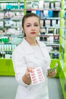 Farmaceuta trzymający blistry i banknoty dolarowe