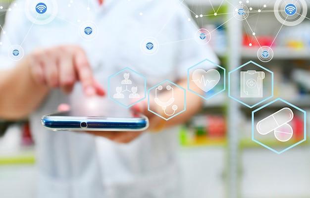 Farmaceuta używający smartfona mobilnego do wyszukiwania paska wyszukiwania na półkach apteki w aptece