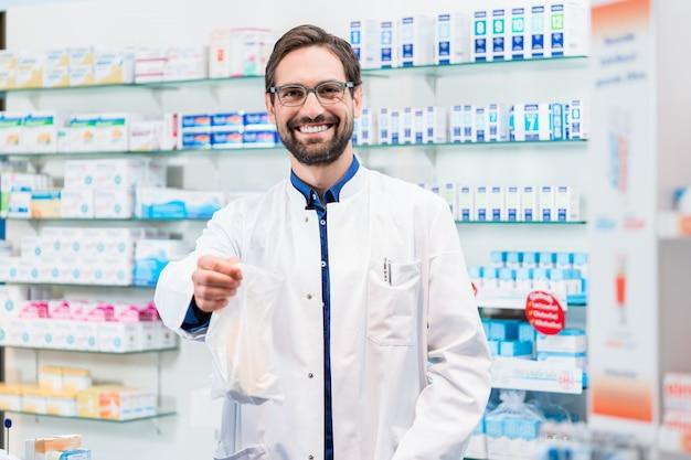 Farmaceuta w aptece sprzedawanie farmaceutyki w torbie