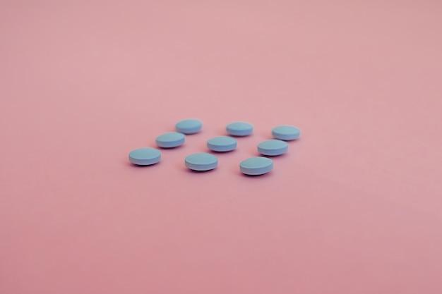 Farmaceutyczne niebieskie pigułki i tabletki na różowo, widok z góry