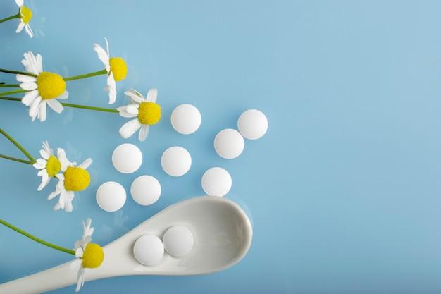 Farmaceutyczne pigułki medyczne, żółte pigułki i kwiaty rumianku