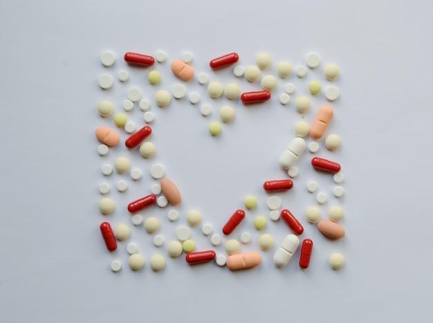 Farmakologia różne pigułki medycyny, tabletki i kapsułki serce miłość rama.